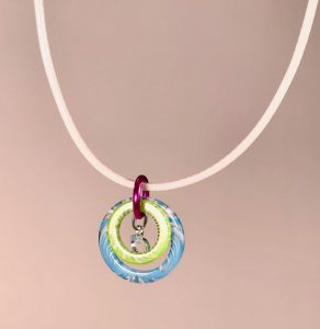 Colors of summer necklace with resin rings and sterling silver heart, on a white cord