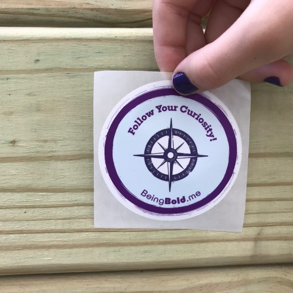 Hand holding a sticker that says Follow Your Curiosity and has compass in the center, surrounded by a purple paint swoop.