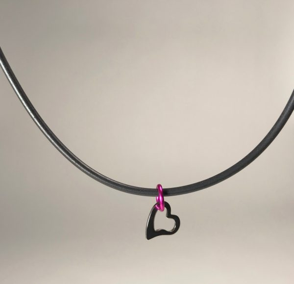 A stainless steel, open heart hangs from a hot pink mettalic loop on a rubber cord.