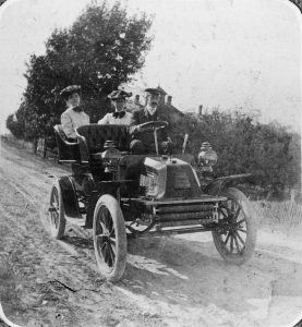Katharine Wright (center), with brother Orville Wright driving and family friend Harriet Stillman on the left side of the photo. Photo from 1903. The car is on a packed dirt road and they seem to have stopped for a photo.