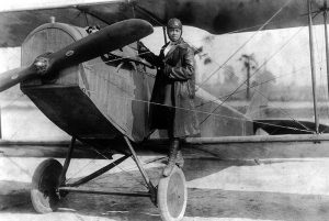 Bessie Coleman in 1922. In this black and white photo, she stands on the wheel of a biplane with a propeller.