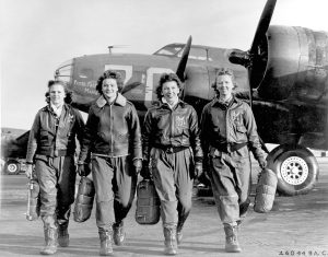 Four women pilots of the Women Airforce Service Pilots, or WASP. The women are walking away from a Boeing B-17 Flying Fortress.