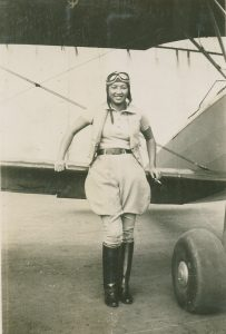 Hazel Ying Lee, in a photo from 1932. Lee served in the WASP. She's standing in front of the wing of a plane that's on the ground.