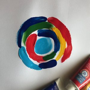 Art Project by Elaine Luther, showing a preschool finger painting project in the style of Sonia Delaunay. Concentric arcs radiate out from a central circle. In the corner, some tubes of paint are visible.
