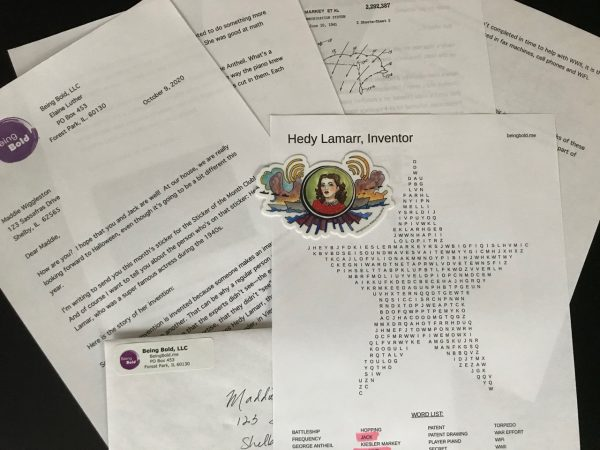 Being Bold Sticker of the Month Club. Image shows a letter, patent drawings, vinyl sticker, word search and an envelope.