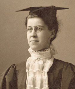 Katharine Wright, pictured in 1898. In this sepia tone portrait she is wearing a graduation cap and gown.