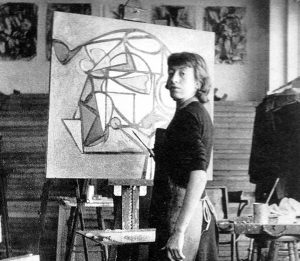 Painter Lee Krasner stands at the easel, she turns slightly to look at the photographer. An abstract painting is on the easel. The photo is black and white and was taken in 1939.