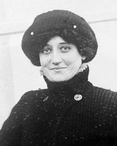 Pilot Raymonde de Laroche in 1909. In this black and white photo, the pilot wears a turtleneck sweater and warm hat as she smiles at the camera. As cockpits were open at that time, she may be dressed this way to stay warm while flying.
