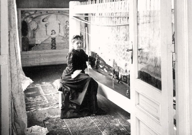 Norwegian weaver Frida Hansen, seated on a low stool at her upright loom. Black and white photo.